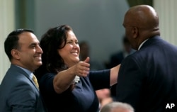 """Assemblywoman Lorena Gonzalez Fletcher, D-San Diego, flanked by Assemblyman Ash Kalra, D-San Jose, left, goes to hug Assemblyman Jim Cooper, D-Elk Grove, for his vote for the """"sanctuary state"""" bill she carried in the Assembly, Sept. 15, 2017, in Sacramento, Calif. The Assembly approved the bill, SB54, by Senate President Pro Tem Kevin de Leon, D-Los Angeles, and Gov. Jerry Brown signed it into law Oct. 5, 2017."""