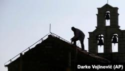 ILUSTRACIJA - Radnik popravlja krov na Crkvi svete nedelje u blizini Svetog Stefana (Foto: AP/Darko Vojinović)