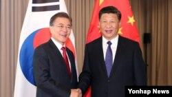 문재인(왼쪽) 한국 대통령과 시진핑 중국 국가주석이 지난달 7일 독일 베를린 주요20개국(G20) 정상회의장에서 만나 악수하고 있다.