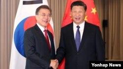 문재인 한국 대통령(왼쪽)과 시진핑 중국 국가주석이 지난달 6일 독일 베를린에서 열린 정상회담에서 악수하고 있다.