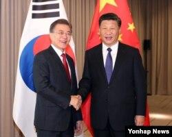 문재인 한국 대통령과 시진핑 중국 국가주석(왼쪽부터)이 6일 독일 베를린에서 열린 정상회담에서 악수하고 있다.