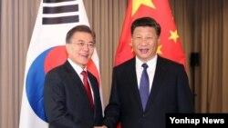 문재인 한국 대통령(왼쪽부터)과 시진핑 중국 국가주석이 6일 독일 베를린에서 열린 정상회담에서 악수하고 있다.