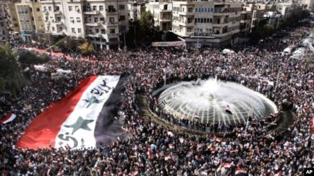 Pro-Syrian regime protesters, carry a giant Syrian flag during a demonstration against the Arab League decision to suspend Syria, in Damascus, Syria, November 13, 2011.