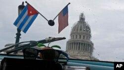 Banderas de Cuba y Estados Unidos decoran el interior de un automóvil estadounidense clásico utilizado como taxi que pasa por el Capitolio de La Habana, Cuba, el viernes 16 de enero de 2015.