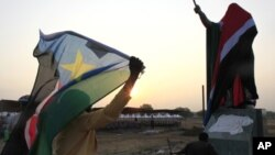 A woman carries a South Sudan flag as she arrives at the John Garang Mouselium for the Independence Day celebrations in the capital Juba July 9, 2011.