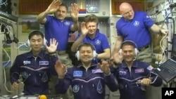FILE - In this image taken from video from NASA, astronauts, front row from left, Kimiya Yui, of Japan, Oleg Kononenko, of Russia, and Kjell Lindgren, of the United States, wave after they boarded the International Space Station, July 23, 2015. The three crew members boarded a Russian Soyuz capsule on Friday for an express ride back to Earth.