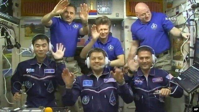 FILE - In this image taken from video from NASA, astronauts, front row from left, Kimiya Yui, of Japan, Oleg Kononenko, of Russia, and Kjell Lindgren, of the United States, wave after they boarded the International Space Station, July 23, 2015.