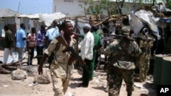 Police and soldiers gather at the site of a suicide blast near the compound of Somali President Sharif Sheikh Ahmed, Mogadishu, March 14, 2012.