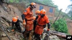 Para petugas pemadam kebakaran mengevakuasi korban tanah longsor di Petropolis, 65 kilometer utara Rio de Janeiro, Brazil (18/3). Sedikitnya 27 orang dilaporkan tewas dalam insiden tanah lonsor ini.