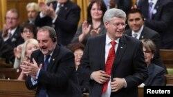 El primer ministro canadiense, Stephen Harper (derecha) vota la moción de participar en la coalición contra el grupo Estado islámico.