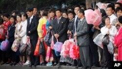 북한 노동당 창건 70주년을 하루 앞둔 8일 장식용 꽃을 든 평양 주민들이 정거장에서 버스를 기다리고 있다.