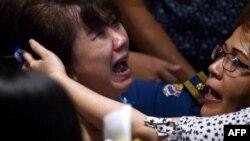 Familiares de los pasajeros del vuelo AirAsia que se precipitó en Indonesia reaccionaron con pesar ante la noticia.