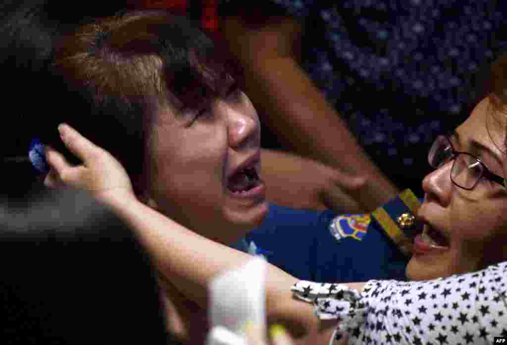 Family members of passengers onboard the missing Malaysian air carrier AirAsia flight QZ8501 react after watching news reports showing an unidentified body floating in the Java sea, inside the crisis center set up at Juanda International Airport in Surabaya, Indonesia.