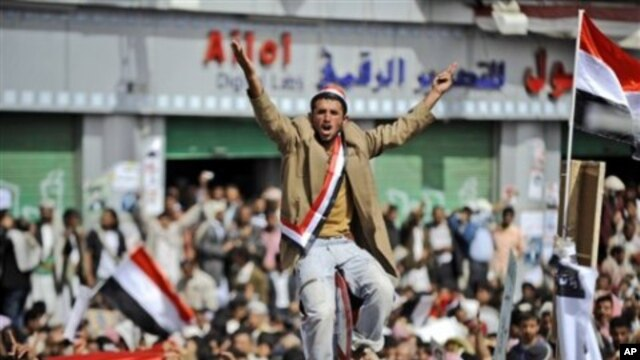 An anti-government protestor sitting on a traffic sign reacts as the bodies of demonstrators who were killed on Friday's clashes with Yemeni security forces, arrive during their funeral procession in Sanaa, Yemen, March 20, 2011