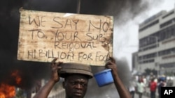 A protester carries a placard on the second day of a protest against a removal of fuel subsidies in Lagos, January 10, 2012.