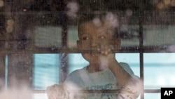 ARCHIVO - Un niño inmigrante mira desde un autobús de la Patrulla Fronteriza de EE.UU. que sale del Centro de Procesamiento Central de la Patrulla Fronteriza de EE.UU. En McAllen, Texas, el 23 de junio de 2018.