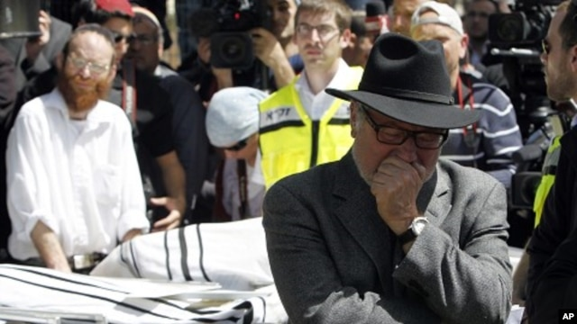 A mourner reacts during a joint funeral in Jerusalem for the victims of Monday's shooting in Toulouse, March 21, 2012.