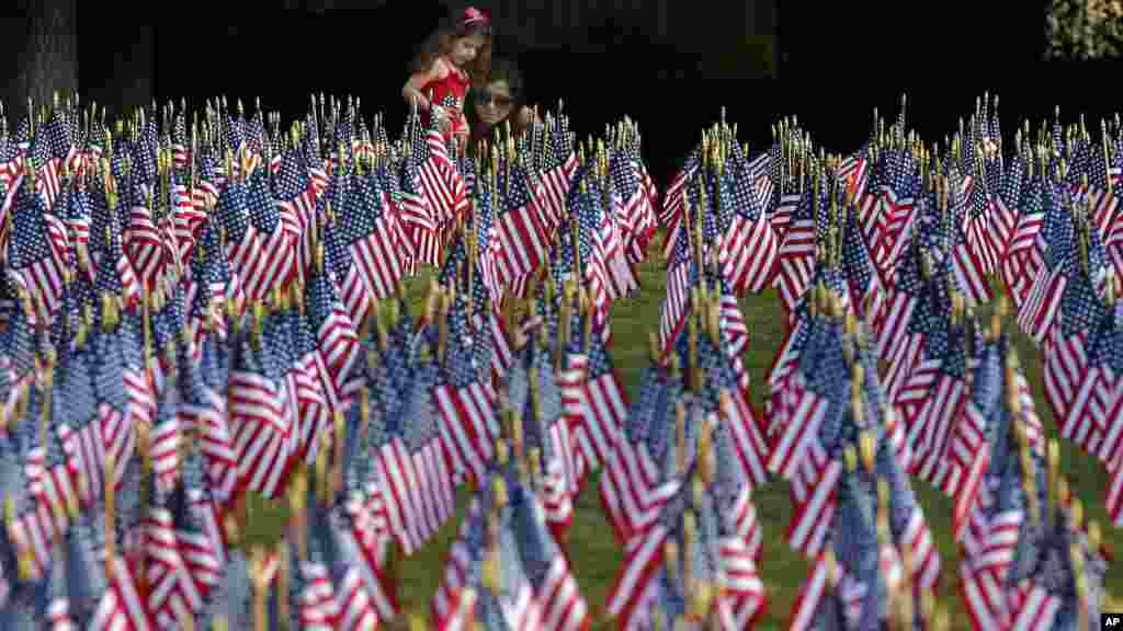 Sophia Demos sits with her daughter, Evniki Tsokanis, 4, among a sea of American flags during a memorial in Matthews, N.C., on the 13th anniversary of the 9/11 terrorist attacks.