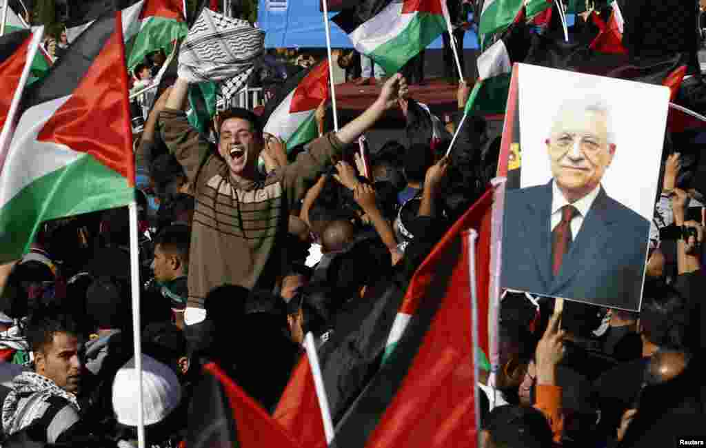 "A Palestinian man cheers near a placard depicting President Mahmoud Abbas during a rally marking the U.N. General Assembly's upgrading of the Palestinians' status from ""observer entity"" to ""non-member state"", in the West Bank city of Ramallah December 2."