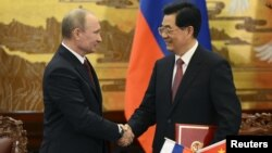 China's President Hu Jintao and Russian President Vladimir Putin shake hands in Beijing, June 5, 2012.