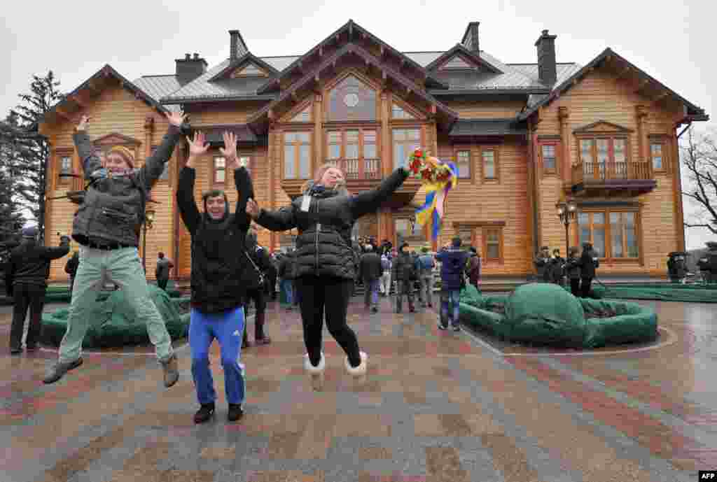 People express their joy in front of the main building of Ukrainian President Viktor Yanukovych's residency near Kyiv. Ukraine's parliament voted to dismiss President Viktor Yanukovych and called for early presidential elections on May 25, but the embattled leader said he would not resign or leave the country.