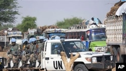 Rwandan troops with the UN-African Union peacekeeping operation in Darfur [UNAMID] escort returnees during a repatriation operation for more than 200 displaced families returning from Aramba to their original village in Sehjanna, north Darfur, Sudan, July