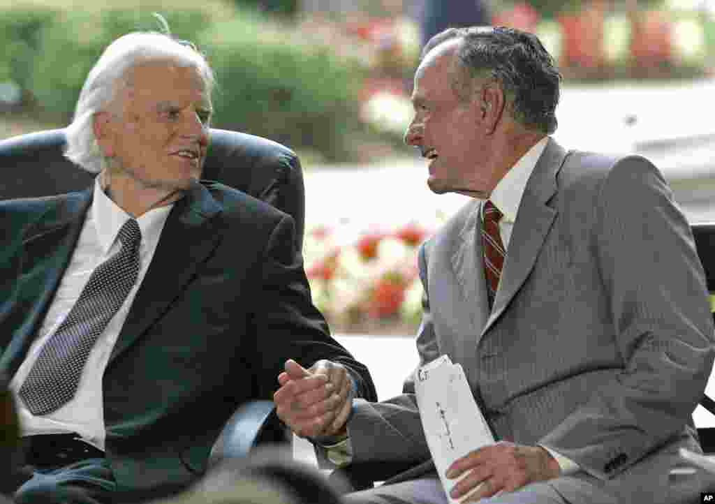 Former President George H.W. Bush, right, takes Billy Graham's hand during a ceremony for the Billy Graham Library in Charlotte, N.C., May 31, 2007.