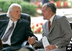 FILE - Former President George H.W. Bush, right, takes Billy Graham's hand during a ceremony for the Billy Graham Library in Charlotte, N.C., May 31, 2007.
