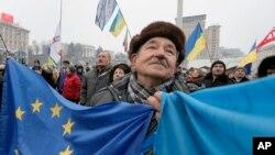 Seorang aktivis pro - Uni Eropa membentangkan bendera Uni Eropa dan Ukraina dalam demonstrasi di Kiev, Ukraina, 20/12/ 2013.