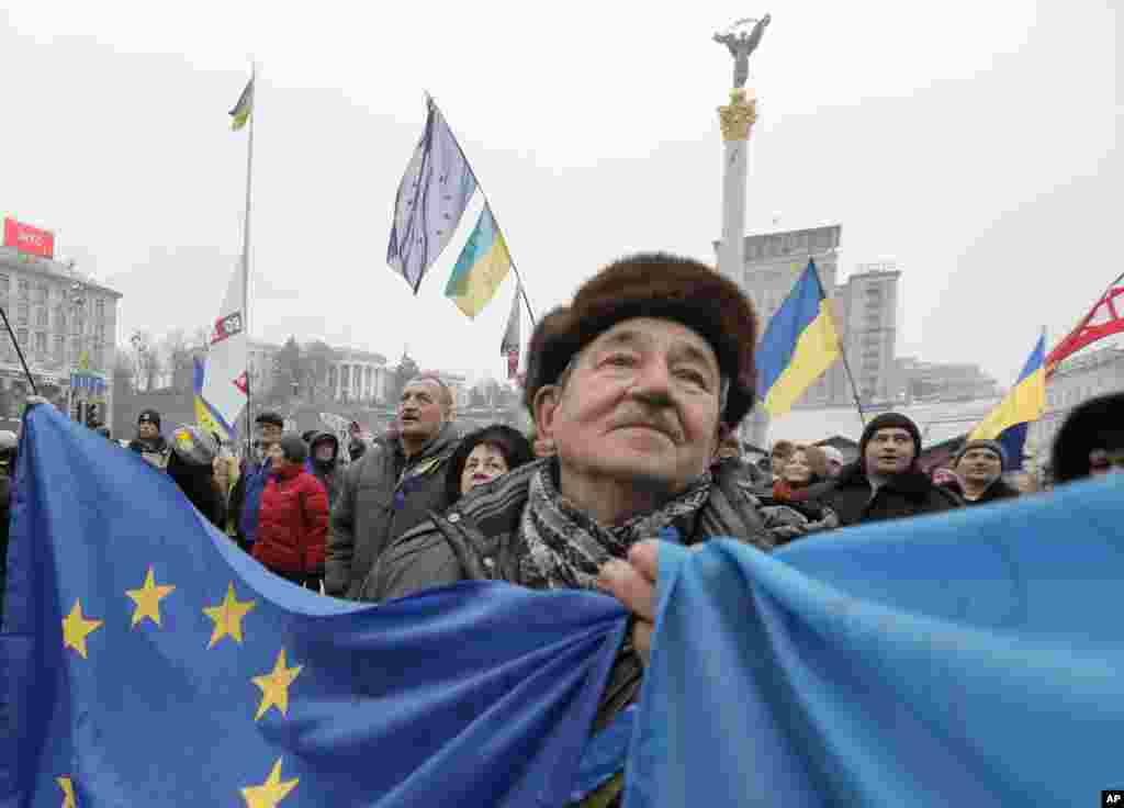 A pro-European Union activist with Ukrainian and the European Union flags stands with others in Independence Square in Kyiv, Ukraine.