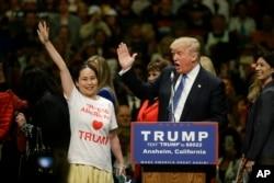 ຜູ້ສະໝັກແຂ່ງຂັນ ເປັນປະທານາທິບໍດີ ສັງກັດພັກຣີພັບບລີກັນ ທ່ານ Donald Trump ແລະ ຜູ້ສະໜັບສະໜູນ ອາເມຣິກັນ ເຊື້ອສາຍເອເຊຍ ຄົນໜຶ່ງ ຍົກມືທັກທາຍ ພວກສະໜັບສະໜູນ ໃນງານໂຮມຊຸມນຸມ ຢູ່ທີ່ ສູນກາງກອງປະຊຸມໃຫຍ່ ໃນນະຄອນ Anaheim, ວັນທີ 25 ພຶດສະພາ 2016.