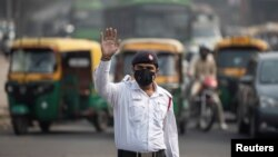 FILE - A traffic policeman wears a mask to protect himself from air pollution at a junction during restrictions on private vehicles based on registration plates, on a smoggy morning in New Delhi, India, November 4, 2019. (REUTERS/Danish Siddiqui)