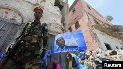Wani sojan gwamnatin Somaliya yana wucewa a kusa da wata mace rike da kwalin fasta na yakin neman zaben shugaba Sheikh Sharif Ahmed