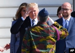 US President Donald Trump, second left, salutes a Belgian soldier as he arrives at Melsbroek Military Airport in Belgium, May 24, 2017. At right is Belgian Prime Minister Charles Michel.
