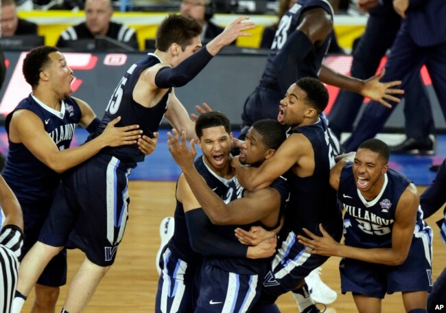 Villanova players celebrates after Kris Jenkins, center, made the game-winning basket as they defeated North Carolina 77-74 in the championship game of the 2016 NCAA Final Four college tournament. (AP Photo/Charlie Neibergall, File)