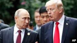 U.S. President Donald Trump and Russia's President Vladimir Putin talk during a photo session at the APEC Summit in Danang, Vietnam, Nov. 11, 2017.