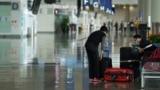 一位女乘客在香港國際機場整理行李(資料照:2020年10月20日)