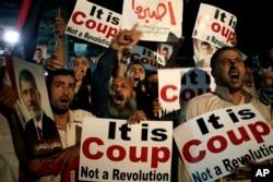 Supporters of Egypt's ousted President Mohammed Morsi chant slogans against Egyptian Defense Minister Gen. Abdel-Fattah el-Sissi at Nasr City, July 28, 2013.
