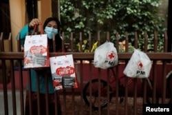 Seorang ibu yang sedan menjalani isolasi mandiri bersama suaminya yang terinfeksi Covid-19, mengambil paket bantuan yang diletakkan di pagar rumah mereka di Jakarta, 3 Agustus 2020. (Foto: Willy Kurniawan/Reuters)