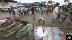 Residents pass by bodies recovered from flashflood in New Bataan, Compostela Valley province, southern Philippines, December 5, 2012.
