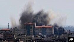 Api membubung setelah serangan misil Israel di kota Gaza (15/7). (AP/Adel Hana)