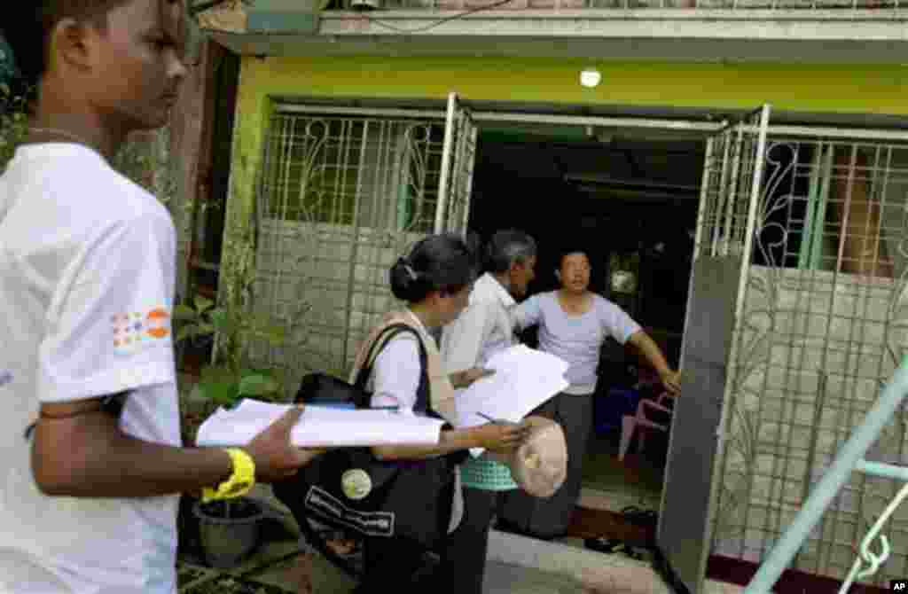 A Myanmar census enumerator and volunteers enter a house to collect information in Yangon, Myanmar, Sunday, Mar 30, 2014. Enumerators fanned out across Myanmar on Sunday for a census that has been widely criticized for stoking religious and ethnic tension