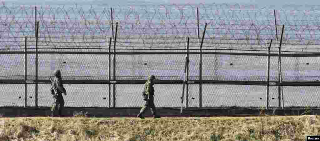 韓國士兵2013年4月7日在韓國首爾以北坡州沿著靠近分隔韓國和朝鮮的非軍事區的軍事圍欄巡邏。