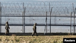韓國士兵2013年4月7日在韓國首爾以北坡州沿著靠近分隔韓國和朝鮮的非軍事區的軍事圍欄巡邏