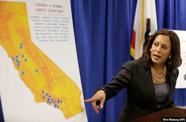 In this March 24, 2016 photo, then-California Attorney General Kamala Harris points to an image showing the location of Corinthian Colleges located in California during a news conference in San Francisco.