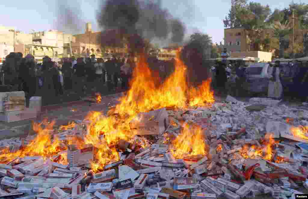 Fighters from Islamic State in Iraq and the Levant burn confiscated cigarettes in the city of Raqqa, April 2, 2014.