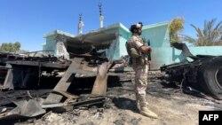 Seorang anggota pasukan keamanan Irak berdiri di dekat kendaraan yang hancur di distrik al-Baghdadi, provinsi al-Anbar, 8 Juli 2021. (Ayman HENNA / AFP)