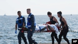 """受伤的""""菲兹杰拉德""""号导弹驱逐舰海军士兵被抬走。"""