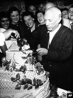Pablo Picasso, famed Spanish painter, accepts first piece of 67-pound birthday cake as he celebrates his 75th birthday, with a birthday party at Vallauris in southern France on Oct. 24, 1956.