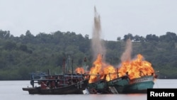 FILE - Malaysian and Vietnamese fishing boats are destroyed for illegal fishing by the Ministry of Maritime Affairs and Fisheries, police and navy, in Batam, Riau Islands, Indonesia, April 5, 2016. The Indonesian government reportedly sank 28 illegal foreign fishing boats simultaneously in nine locations across the country.